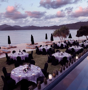 Eight round dinner tables with silver table cloths and chairs facing qualia resort pool lounges and the Whitsundays