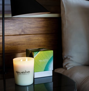 Candle and its box with 'qualia' engraving on side table at qualia resort