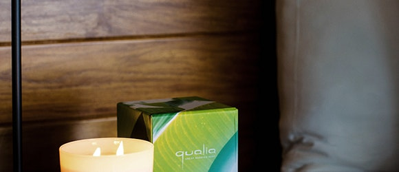 Candle and candle box with 'qualia' inprint on side table at qualia resort