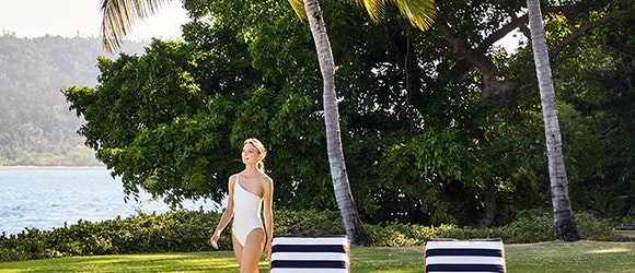 Woman in white swimsuit walking past two striped sun lounges by the Pebble Beach pool at qualia resort