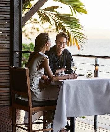 Couple enjoying wine and Whitsundays views at dinner table at qualia resort restaurant Pebble Beach