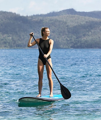 Woman enjoying qualia resort experience of stand up paddle boarding