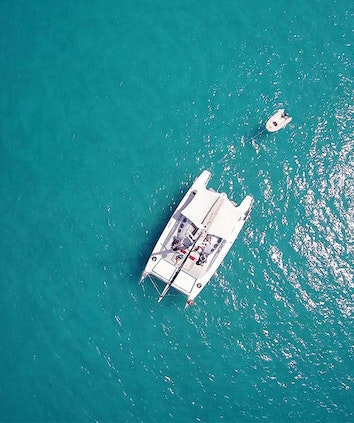 Aerial view of Ricochet luxury catamaran with floating boat attached as part of qualia luxury experience