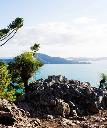 Rocky outcrop and Whitsunday islands views behind it as part of qualia bushwalking experience