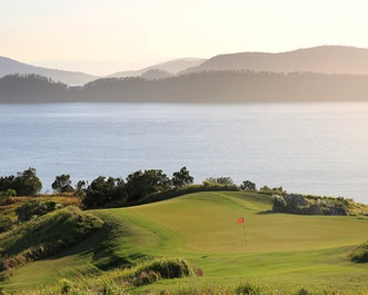 qualia view of red pin on Dent Island Golf course with sunlight pouring from the Whitsundays