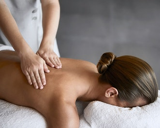 Woman receiving a back massage by spa therapist as part of spa qualia treatment