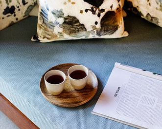 Tray with two cups of tea and a magazine with page titled tea titans at spa qualia