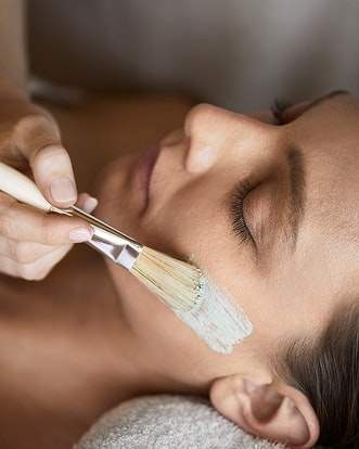 Woman receiving spa treatment facial at spa qualia
