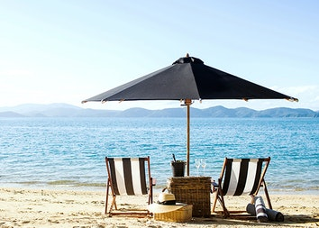 qualia Pebble Beach with sun lounges under umbrellas on the sand and views of the Whitsundays