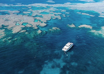 qualia resort aerial view of luxury boat amongst Great Barrier Reef for diving and snorkelling