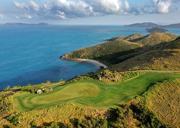 qualia aerial view of Dent Island Golf Course with rolling hills surrounded by Whitsundays