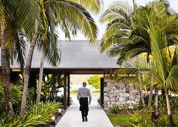 Waiter walking through garden path at qualia resort restaurant Pebble Beach