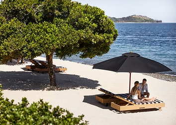 qualia resort guest couple sitting on sun lounges at Pebble Beach with Whitsundays views
