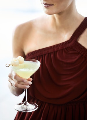 Close up of woman in maroon dress holding lychee martini cocktail at Long Pavilion bar at qualia