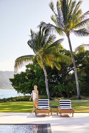 Woman in white bathing suit walking across qualia Pebble Beach pool lounges