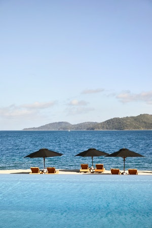 View of pool lounges under umbrellas and qualia's Pebble Beach from infinity pool