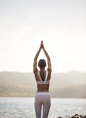 Woman with hands in prayer above head during sunrise yoga at spa qualia with view of Pebble Beach