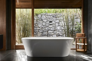 View of white bathtub and stonewall at qualia Beach House bathroom