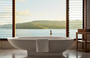 Raised modern bathtub in qualia Windward Pavilion with views of Whitsundays through window