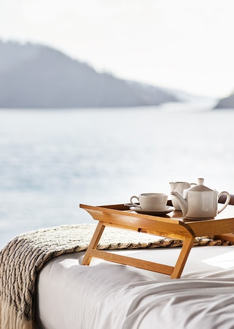 Wooden tray with teapot, cup and saucer on bed with expansive views through window of the Whitsundays