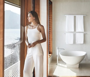 Woman standing in qualia Windward Pavilion bedroom looking at Whitsunday views with bathtub in background