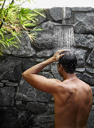 Man enjoying outdoor shower facing stone wall at spa qualia