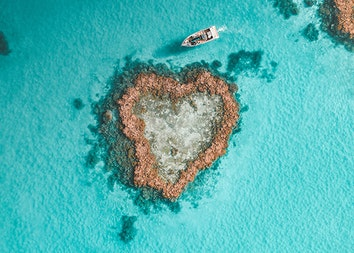 qualia resort activity of luxury Heart Island experience showing aerial of boat amongst reef