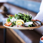 Waiter carrying seafood lunch dish at qualia resort restaurant Pebble Beach in the Whitsundays