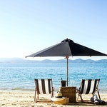 qualia resort luxury Beach Drop Off Experience with two sun chairs and umbrella on the beach