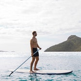 Man enjoying qualia resort experience of stand up paddle boarding at Catseye Beach