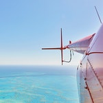 Side view of a red helicopter and its tail rotor over the Great Barrier Reef as part of qualia scenic flight experience