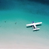 Aerial view of a seaplane in the turquoise waters of Whitehaven Beach