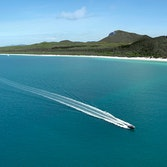 Aerial view of boat and its wake in the Whitsundays as part of qualia boating experience at Whitehaven Beach