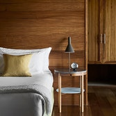 Bed with lamp and alarm clock on side table and wooden wall panelling in qualia resort Leeward Pavilion bedroom