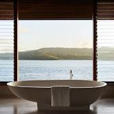 Raised modern bathtub in qualia Windward Pavilion with views of Whitsundays through window