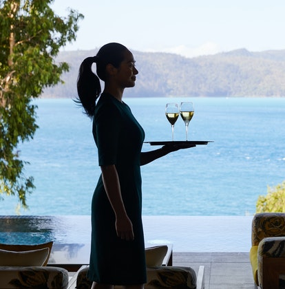 qualia Attendant in Long Pavilion Walking with Tray for Welcome Champagne Service