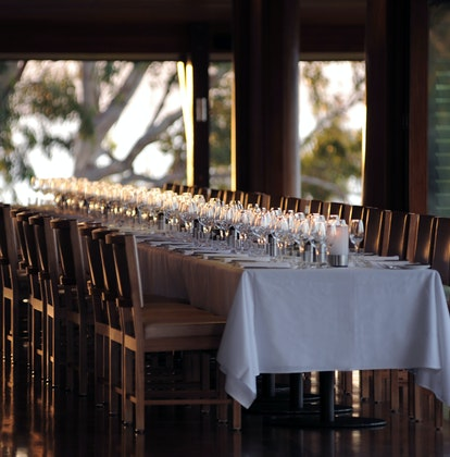 Long table and chairs for corporate retreat with sunlight coming through the window at qualia's Long Pavilion