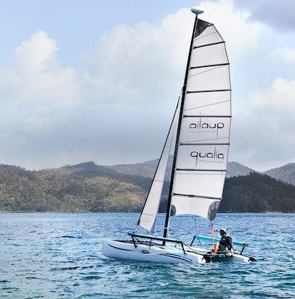 qualia Resort Pebble Beach catamaran with man sailing in the Whitsundays