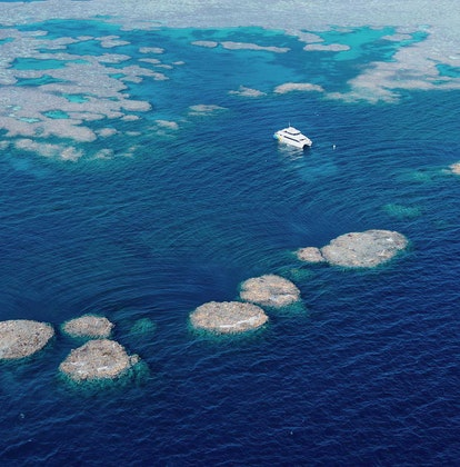 qualia aerial view of luxury boat used for diving and snorkelling amongst stepping stone formations in Great Barrier Reef