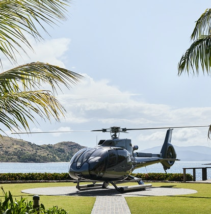 qualia resort helicopter on private helipad surrounded by palm trees and Whitsunday views