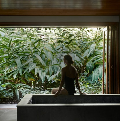 Spa qualia treatment room with woman sitting on bath edge looking out the window to views of lush foliage