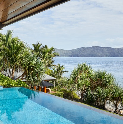 qualia resort Beach House with accordion windows opened up to show infinity pool and Whitsundays views