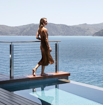 Woman standing on edge of private plunge pool of qualia Windward Pavilion looking at Whitsundays views